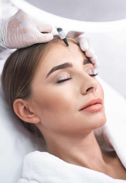 Enjoying the procedure. Close up portrait of smiling young lady with closed eyes. She is getting facial skin lifting treatment at beauty salon