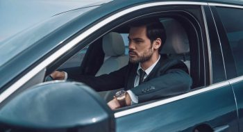 Just keep moving! Handsome young man in full suit looking straight while driving a car