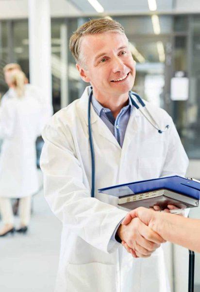 Facharzt beim Hände schütteln mit einer Chirurgin für erfolgreiche Zusammenarbeit